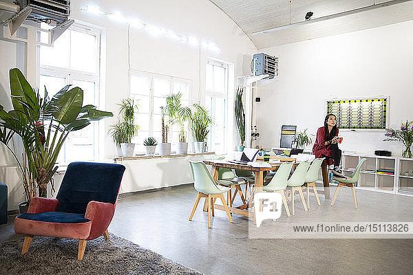 Frau am Tisch sitzend in einem modernen Büro