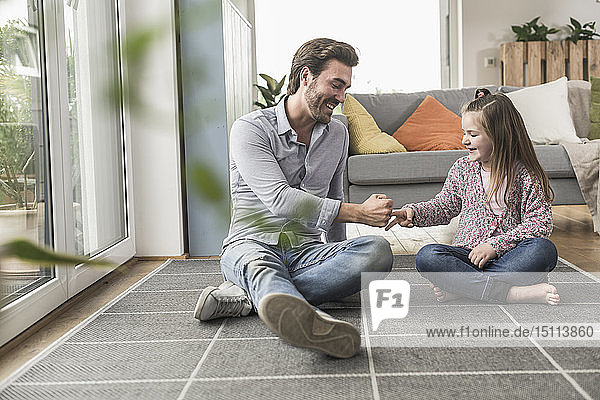 Young man and little girl sitting at home  playing paper scissors stone