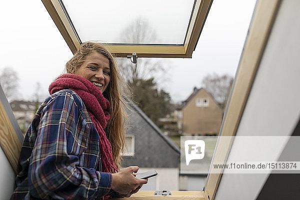 Porträt einer glücklichen jungen Frau am Dachfenster