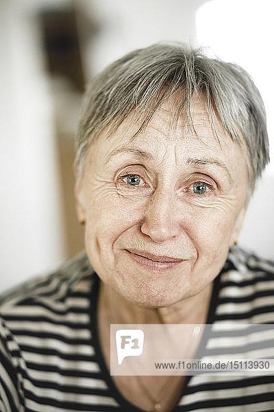 Porträt einer glücklichen älteren Frau mit kurzen Haaren  die mit Tränen in den Augen lächelt
