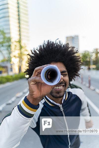 Lächelnder Gelegenheitsarbeiter beim Durchblättern von Zeitungen in der Stadt  Barcelona  Spanien