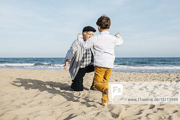 Großvater spielt mit seinem Enkel am Strand