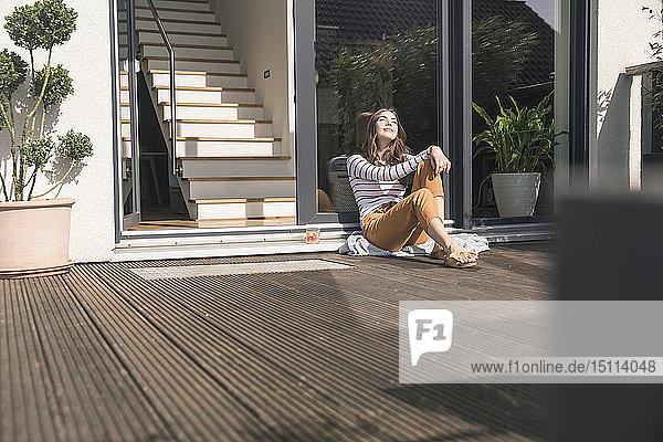 Junge Frau sitzt zu Hause auf der Terrasse und genießt den Sonnenschein