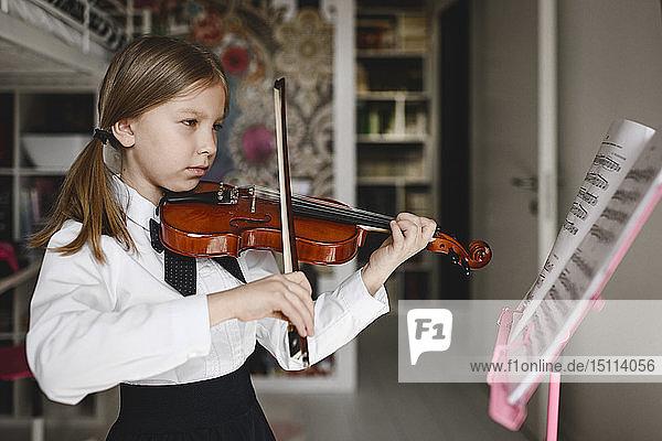 Girl playing violin looking at music stand at home