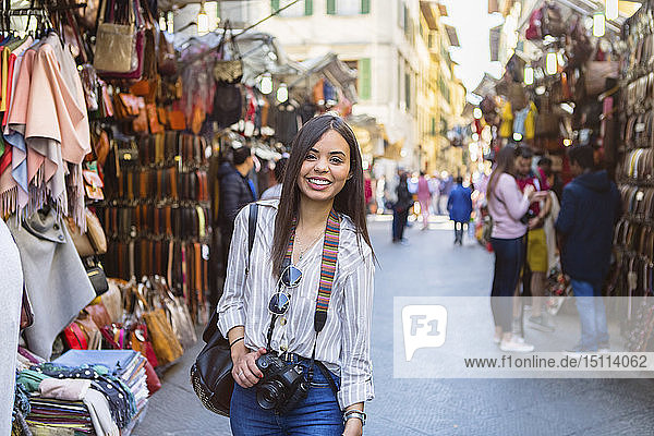 Italy  Florence  portrait of happy young tourist with camera exploring street market