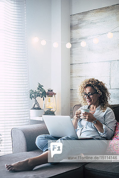 Woman on couch at home with coffee mug and laptop