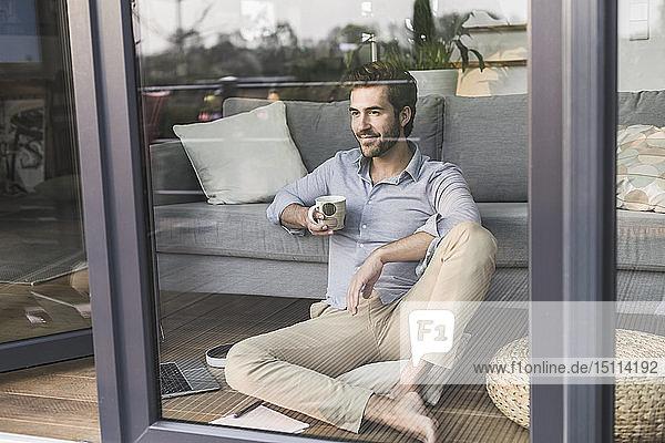 Junger Mann sitzt vor dem Fenster und trinkt Kaffee