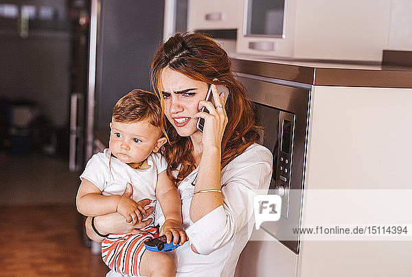 Annoyed mother with her son talking on the phone at home