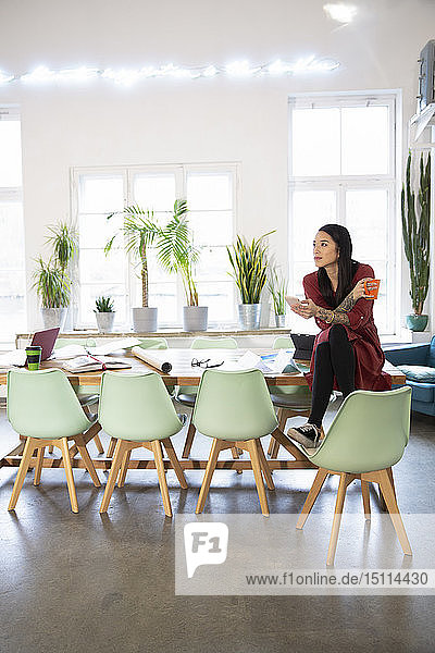 Woman sitting on table in modern office