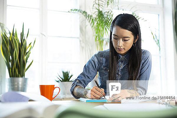 Frau arbeitet am Tisch im Büro und macht Notizen