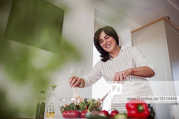 Reife Frau bereitet in ihrer Küche Salat zu