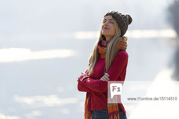 Junge blonde Frau im Winter an einem See