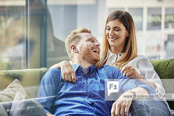 Glückliches Paar auf dem Sofa sitzend  die Arme um den Körper gelegt