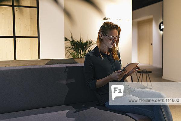 Geschäftsfrau sitzt auf Couch mit Tablett