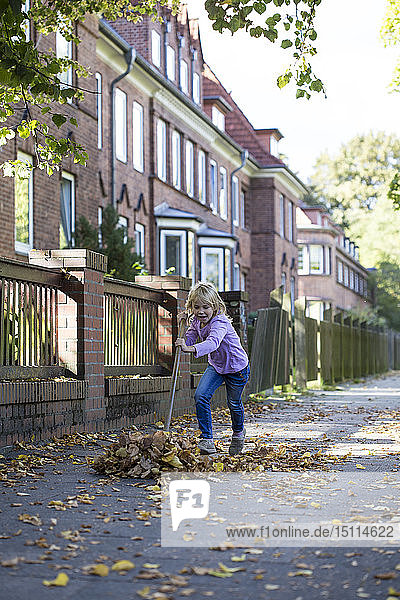 Girl sweeping leaves on pavement