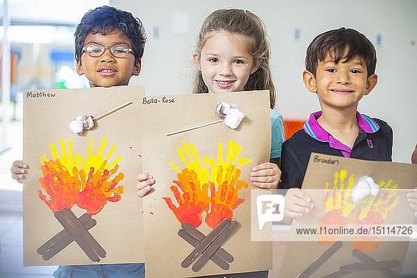 Porträt von lächelnden Kindern  die Bilder von Feuer im Kindergarten präsentieren