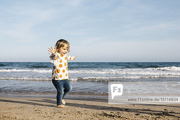 Happy little girl running barefoot on the beach