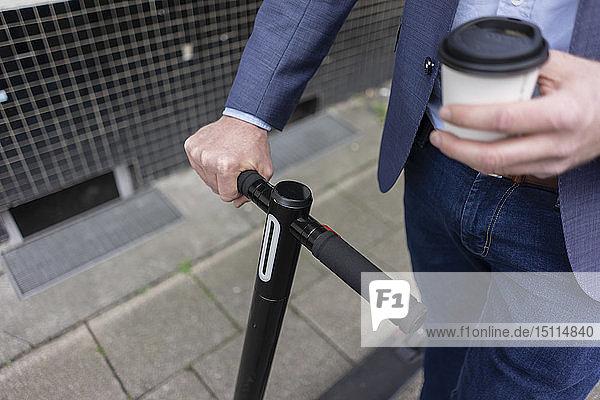 Geschäftsmann mit E-Scooter und Kaffee zum Mitnehmen  Teilansicht