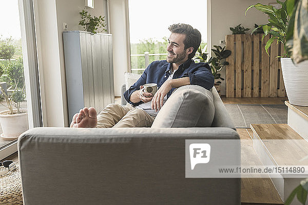 Young man sitting on couch at home  drinking coffee