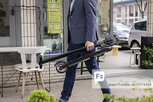 Geschäftsmann mit gefaltetem E-Scooter beim Gehen auf dem Bürgersteig  Teilansicht