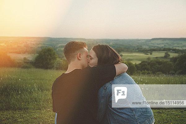 Rückenansicht von glücklichen jungen Verliebten  die sich bei Sonnenuntergang küssen
