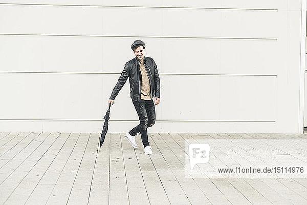 Junger Mann geht um geschlossenen Regenschirm herum