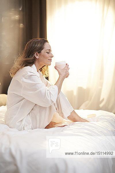 Brünette Frau sitzt auf dem Bett und hält einen Cremetiegel