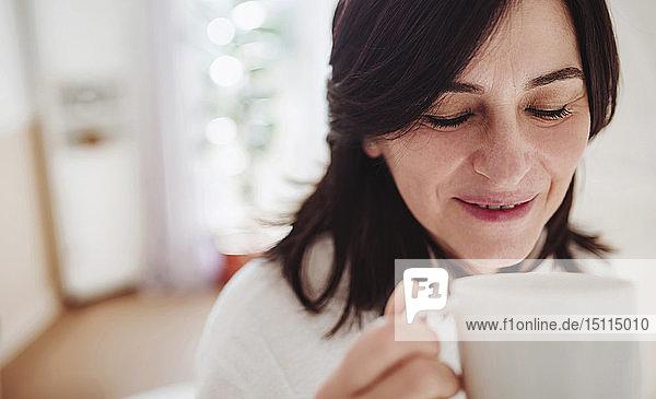 Reife Frau im häuslichen Badezimmer bei einer Tasse Kaffee