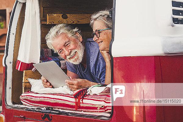 Älteres Ehepaar reist in einem Oldtimer-Van  liegt im Kofferraum und benutzt ein digitales Tablett