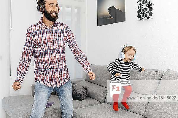 Father and little daughter dancing in the living room while listening music with headphones