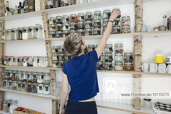 Woman taking jar from spice shelf in kitchen