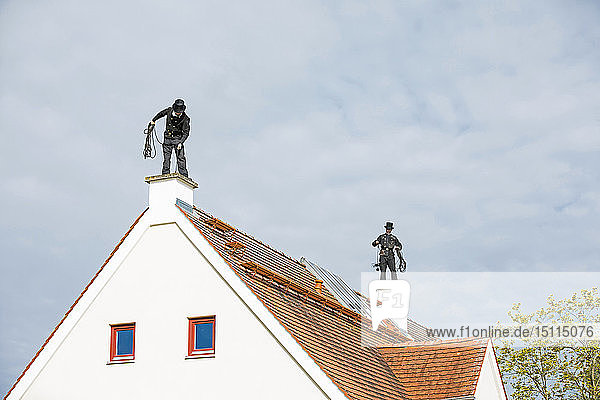 Two chimney sweeps working on house roof