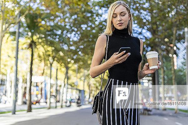 Porträt einer blonden Frau mit Kaffee zum Handy anschauen