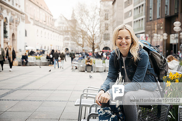Porträt einer lächelnden blonden Frau mit Gepäck in der Stadt  München  Deutschland