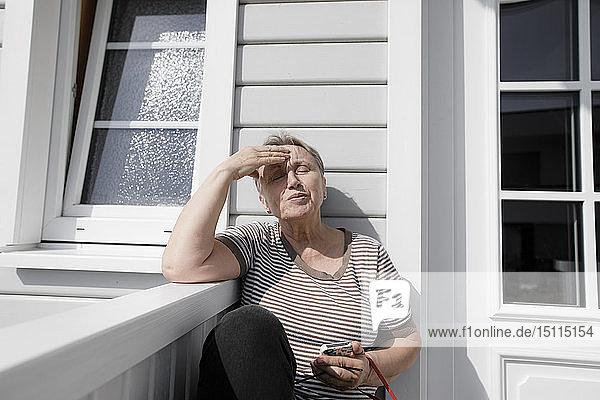 Entspannte ältere Frau sitzt auf der Veranda im Sonnenschein