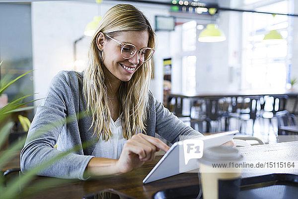 Junge Frau benutzt ihr digitales Tablett beim Kaffeetrinken im Café