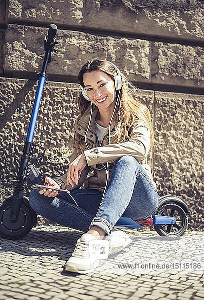 Porträt einer glücklichen Frau  die auf einem E-Scooter sitzt und mit Kopfhörern und Smartphone Musik hört