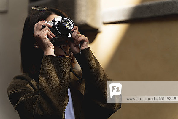 Italy,  Florence,  young tourist woman taking pictures in the city