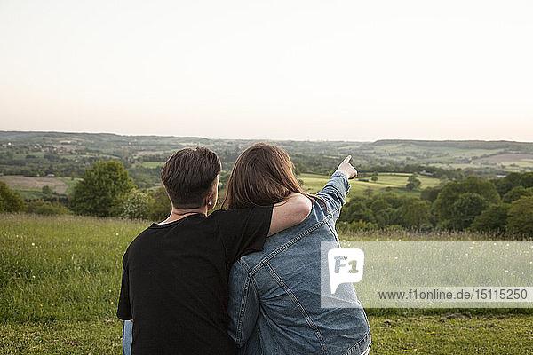 Rückenansicht von glücklichen jungen Liebenden in der Natur beim Anschauen