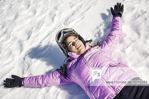 Glückliche Frau  die sich nach dem Skifahren auf dem verschneiten Boden in der Sierra Nevada  Andalusien  Spanien  eine Pause gönnte