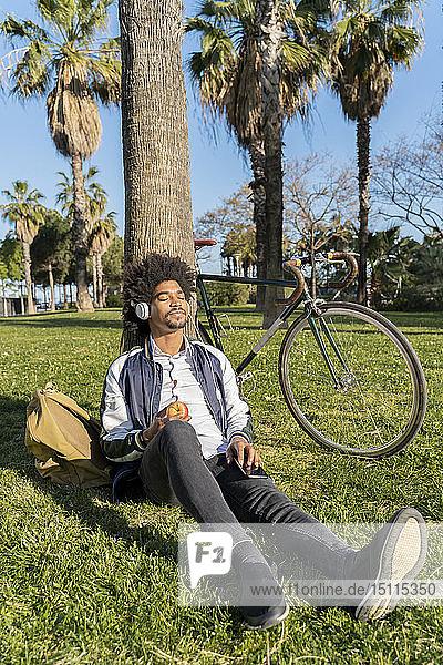 Lässiger Geschäftsmann macht eine Pause im Stadtpark und hört Musik  Barcelona  Spanien
