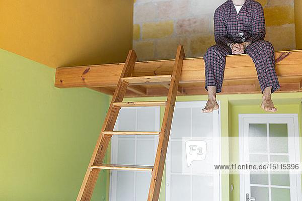 Mann  der zu Hause einen Pyjama trägt und auf einem Hochbett sitzt