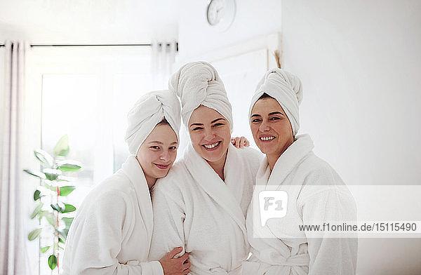 Porträt einer glücklichen reifen Frau mit zwei Töchtern in einem Badezimmer zu Hause