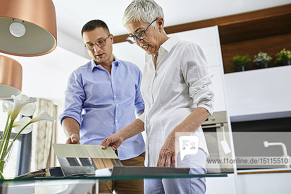 Man and mature woman in a kitchen retail store examining material samples