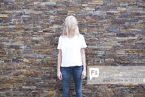 Frau vor Steinmauer  verdecktes Gesicht