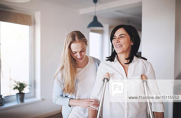 Tochter hilft ihrer Mutter mit Krücken beim Gehen