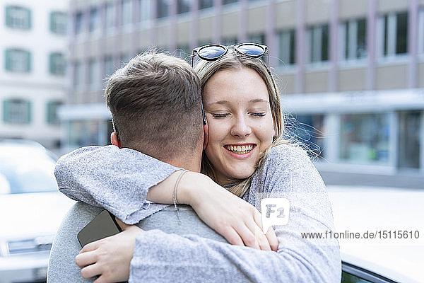 Porträt einer glücklichen jungen Frau  die ihren Freund umarmt