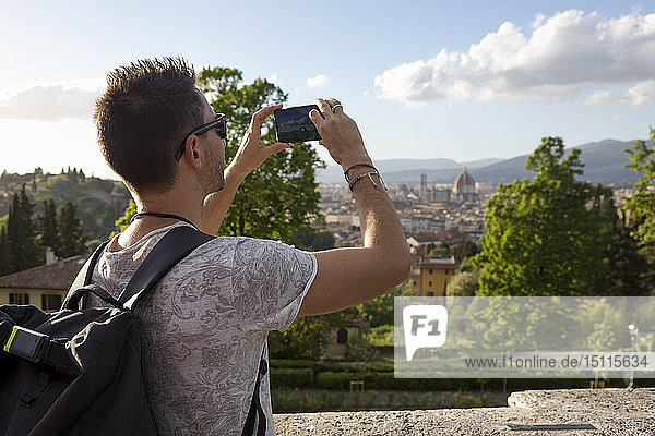 Man taking a photo of Florence with his smartphone  Florence  Italy