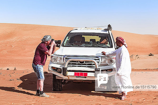Tourist taking pictures of his local driver in the desert,  Wahiba Sands,  Oman