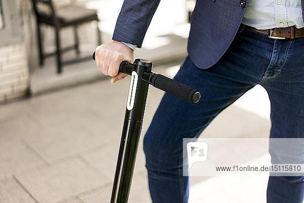 Geschäftsmann mit E-Scooter  Teilansicht